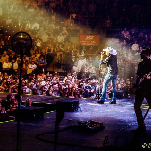 Justin Moore singing in spotlight, crowded arena view