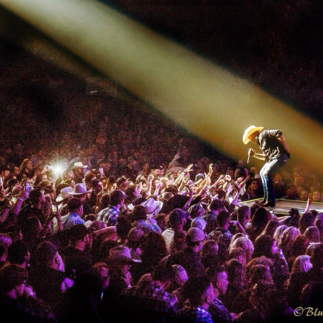 Spotlight on Justin Moore singing while fans wave