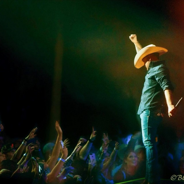 Justin Moore fist raised while fans wave