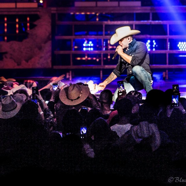 Justin Moore shaking a fans hand at the stage edge while singing.