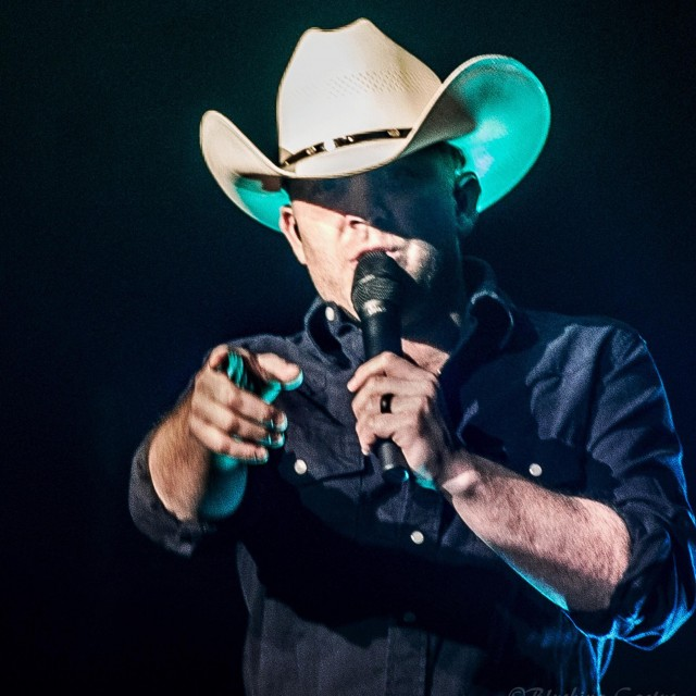 Close up of Justin Moore singing and pointing into camera lens