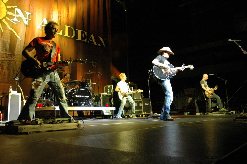 Front Row Shot Of A Country Band Playing Guitars On Stage