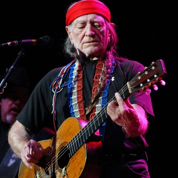 Willie Nelson singing and playing the guitar.